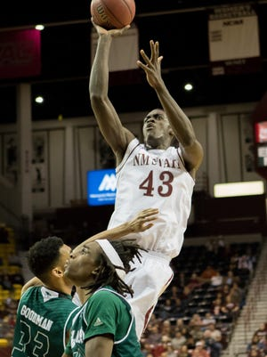 New Mexico State's Pascal Siakam leaps over Utah Valley defenders Saturday night at the Pan American Center.