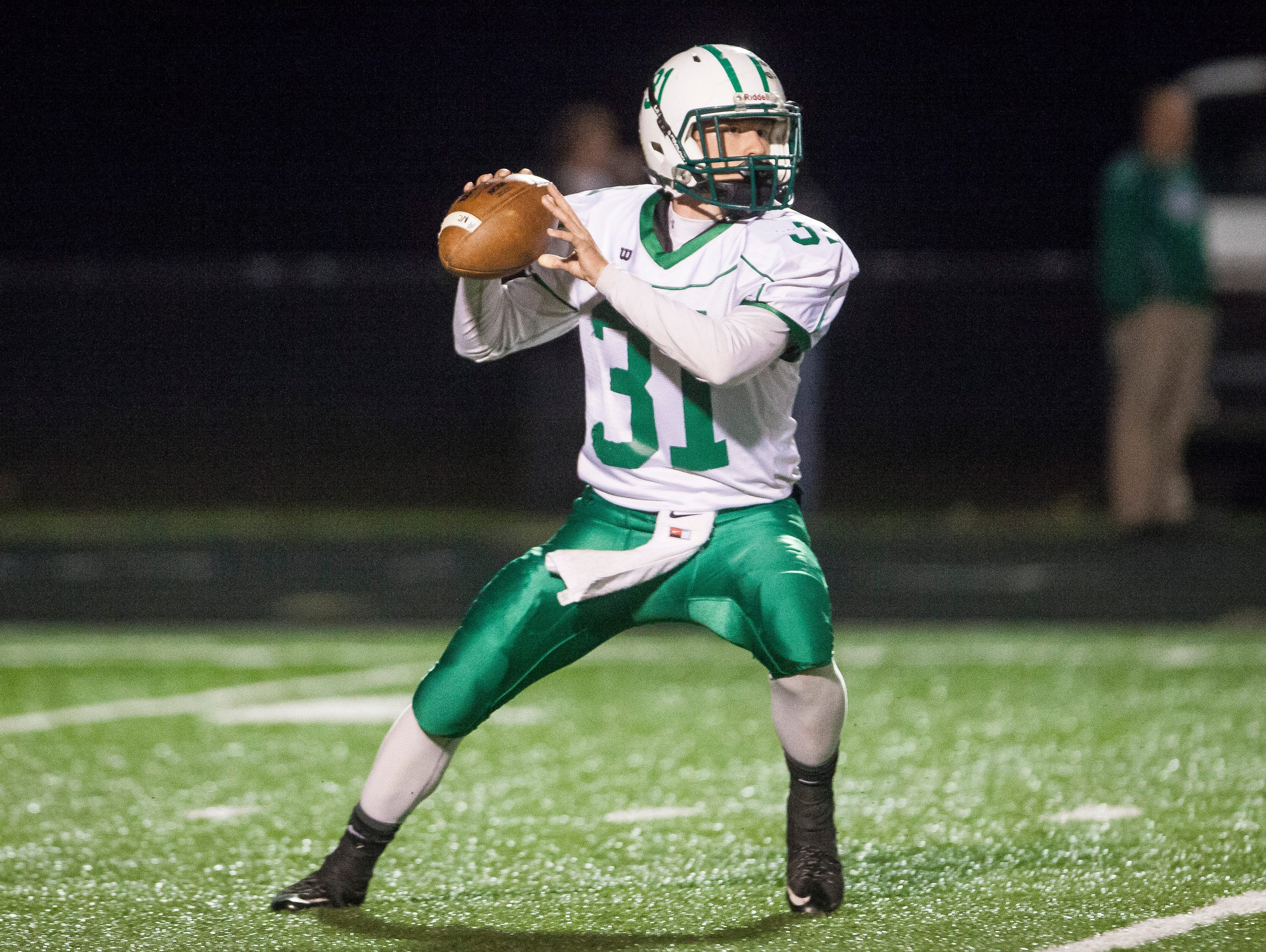 New Castle's Dalton Engle draws back for the pass Friday night during the sectional game at Delta. Delta won 49-7.