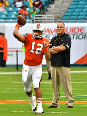 Miami Hurricanes quarterback Malik Rosier (left) warms up as Hurricanes head coach Mark Richt (right) looks on before their game against the Bethune Cookman Wildcats at Hard Rock Stadium.