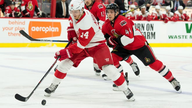 Red Wings right wing Gustav Nyquist (14) skates with the puck in front of Senators cente Jean-Gabriel Pageau (44) in the first period at the Canadian Tire Centre Saturday.