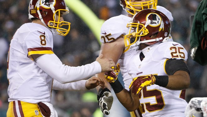 Washington Redskins' Kirk Cousins (8) and Chris Thompson (25) celebrate after Thompson's touchdown in the second half against the Philadelphia Eagles on Saturday.