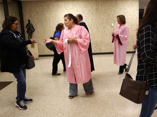 214th District Court Judge Inna Klein (center) hands out breast cancer awareness stickers on Monday, October 2, 2017. Judges hand out stickers and remind people arriving at the courthouse on Monday mornings in October about the need to get a mammogram and to remind their loved ones as well.
