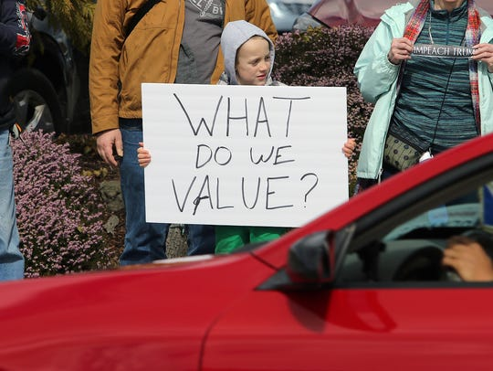 """Colan Poncelow, 7, of Poulsbo holds a sign for passing vehicles to see at the Silverdale """"March For Our Lives """" protest Saturday."""