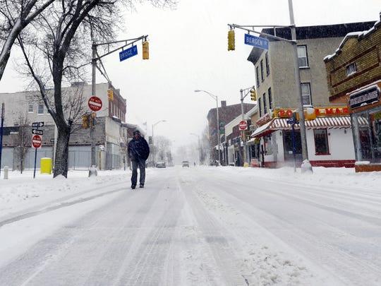 A lone man walks down Main Street in Hackensack, NJ as heavy snow falls on on Thursday, Feb. 09, 2017.