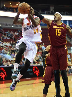Canton Charge's James Singleton (15) tries to block the shot of Iowa Energy's (14) Russ Smith as he drives in for a layup during the first half of the game at Wells Fargo Arena on Sunday, Mar. 29, 2015.