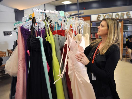 Millville Senior High School guidance counselor Michelle Giercyk places a prom dress back on a rack in the library, Tuesday, Mar. 22, 2016.