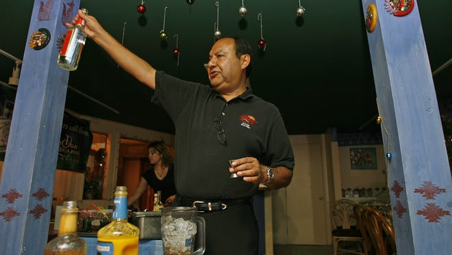Pedro Rosales, owner of La Margarita Company Restaurant, holds a bottle of triple sec aloft while demonstrating the art of making margaritas during a class at the restaurant.
