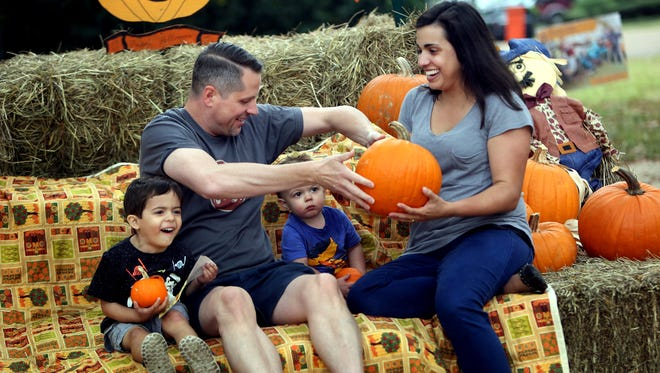 Chris and Kristin Hoffman juggle a pumpkin while their two sons, 3-year-old Owen and 1-year-old Reese, remain focused on having their photograph taken at the 2nd Baptist Pumpkin Patch. The family is enjoying fall break and stopped by the Patch on Thursday morning. In addition to a photo area, the Patch offers pumpkins of various sizes, other gourds, flowers and samples of fresh pumpkin bread. Proceeds from sales go to support the church''s Student Ministry and Student Missions. The church will host a Pumpkin Festival Oct. 22 from 11 a.m. to 1 p.m. Located at 4860 Walnut Grove, the Patch is open M-S 10 a.m. to dusk and Sunday noon to dusk through Oct. 31.