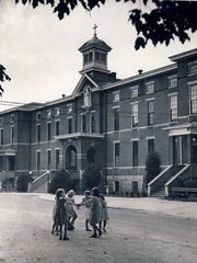 In 1949, girls form a circle in front of St. Joseph's Orphanage, built in 1885 at a cost of $50,000 on Frankfort Avenue in Crescent Hill.