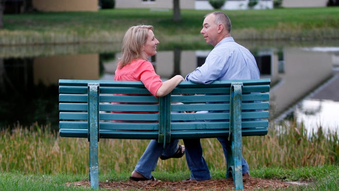 Paul Johnson and Shelly Osterhout, pictured Monday, September 28 sitting on the neighborhood bench where Paul proposed,  are inviting the public to crash their October 10 wedding reception at the Bell Tower Shops.