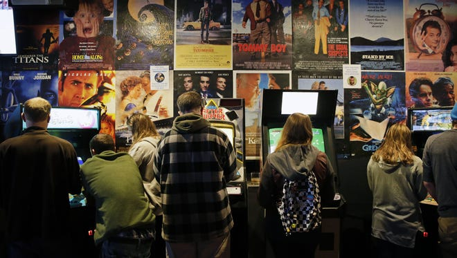 Game players tackle an assortment of video games beneath film posters at Player 2 Arcade Bar in downtown Appleton.