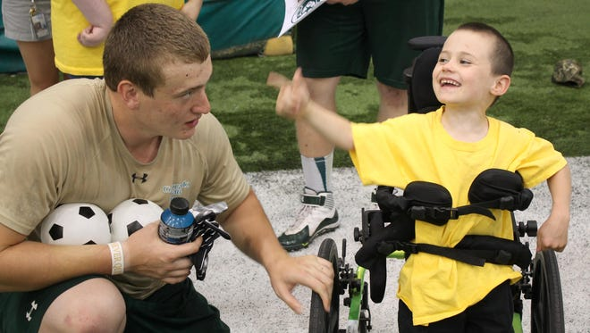 CSU lineman Zach Stefo, left, and Dawson from Respite Care united to fight evil in the Marvel Universe.