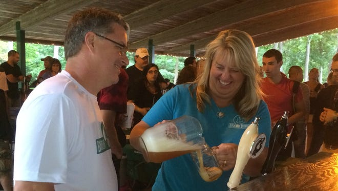 Dennis Edwards and his wife, Susan, from Horseheads, pour samples of their craft beer at Zoo Brew on Saturday at the Binghamton Zoo at Ross Park.