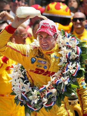 Driver Ryan Hunter-Reay pours the bottle of milk over his head in Victory Circle after winning the 98th Indianapolis 500 on Sunday May 25, 2014.