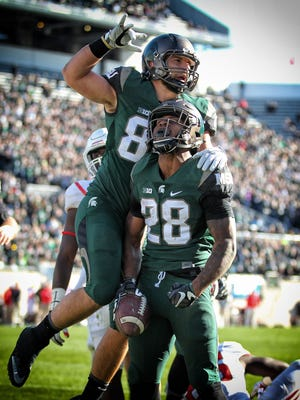 Nov 12, 2016; East Lansing, MI, USA; Michigan State Spartans running back Madre London (28) and tight end Josiah Price celebrate a touchdown against Rutgers at Spartan Stadium.