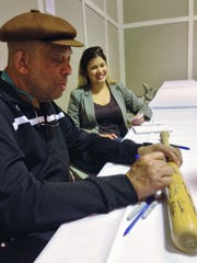 Orlando Cepeda autographs a baseball bat Saturday at