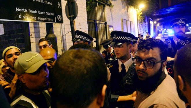 Police officers talk with local people at the Finsbury Park in north London, where a vehicle struck pedestrians Monday. A vehicle struck pedestrians near a mosque in north London early Monday morning, causing several casualties, police said. (Yui Mok/PA via AP)