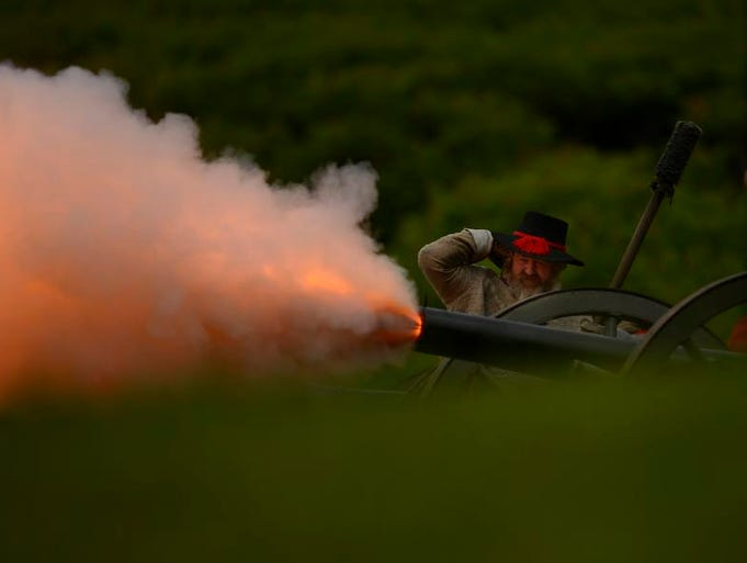 A Confederate soldier plugs his ears as a canon fires during a Civil War Reenactment at Heritage Hill State Historical Park in Allouez on Saturday, June 21, 2014.