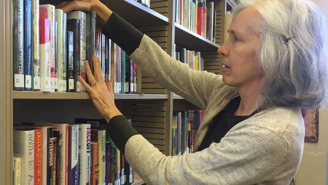 Marilyn Patterson, library services coordinator, arranges books in the fiction section at Waite Park Library. She and other staff are planning a poetry sidewalk in the library's reading garden.