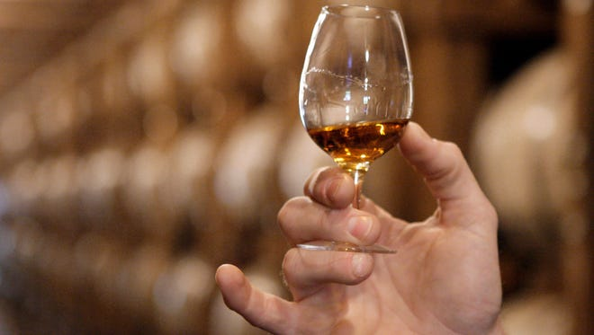 A glass of Jack Daniel's whiskey is examined after being taken from an aging barrel in one of the barrel houses at the distillery in Lynchburg, Tenn. American distilleries large and small have watched warily as rhetoric about tariffs has ratcheted up. Export revenues for bourbon, Tennessee whiskey and rye whiskey products topped $1 billion in 2017, continuing a trend in recent years, according to the Distilled Spirits Council.