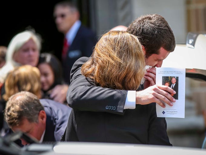 Mourners console each other after the funeral service