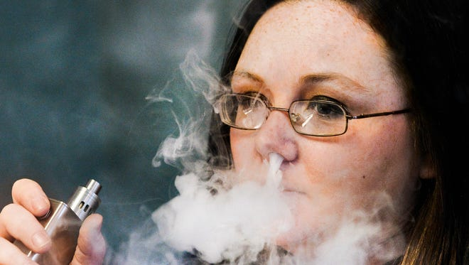In this Wednesday, Feb. 17, 2016 photo, Stephanie Wilson, an employee at Breathe Vapor, a retail shop that specializes in electronic cigarettes, exhales vapor at the store in East Peoria, Ill.