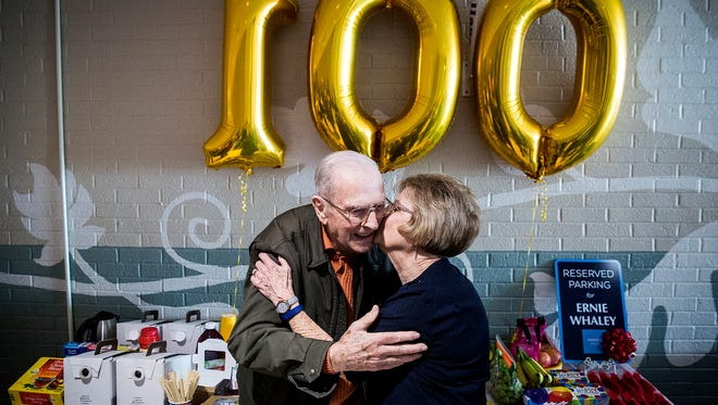 Ernie Whaley, 100, is kissed by a fellow mall walker during his birthday celebration at the Muncie Mall Monday morning.