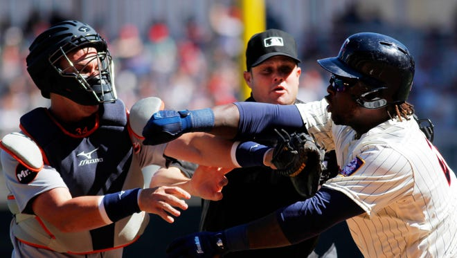 Miguel Sano of the Minnesota Twins and James McCann of the Detroit Tigers clash with home plate umpire Jordan Baker attempting to break up the altercation in the fifth inning on April 22, 2017 at Target Field in Minneapolis.