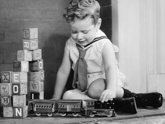 Boy playing with model train set on floor,