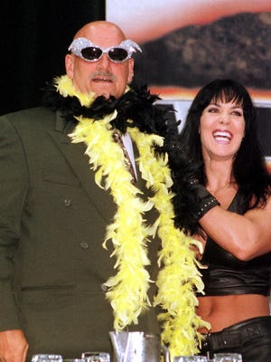 "MINNEAPOLIS, UNITED STATES: Minnesota Governor and former professional wrestler Jesse Ventura (L) is adorned with his former trademarks, sequined sunglasses and a feather boa, by wrestler Chyna during a press conference at the Target Center in Minneapolis, MN 14 June 1999 where he announced that he will return to the ring as guest referee in the SummerSlam wrestling event 22 August 1999 in Minneapolis. Governor Ventura said that ""There's no rule that says a governor can't have fun. There's no rule that says a governor on his own time can't be a human."" AFP PHOTO/CRAIG LASSIG (Photo credit should read CRAIG LASSIG/AFP/Getty Images)"