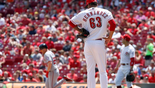 Cincinnati Reds relief pitcher Ariel Hernandez (63) stands at the mound as Washington Nationals first baseman Adam Lind (26) rounds the bases after hitting a two-run home run during the fifth inning at Great American Ball Park on July 16.