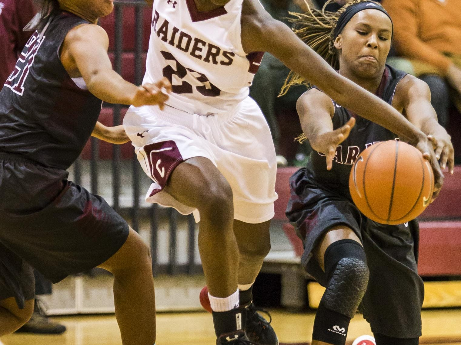Caravel's Sasha Marvel (right) pulls the ball away from Concord's Zhan'e Snow (No. 23) as Snow tries to drive between Marvel and Kaylee Otlowski (left) in the first half of Caravel's 42-26 win over Concord at Concord High School on Monday night.