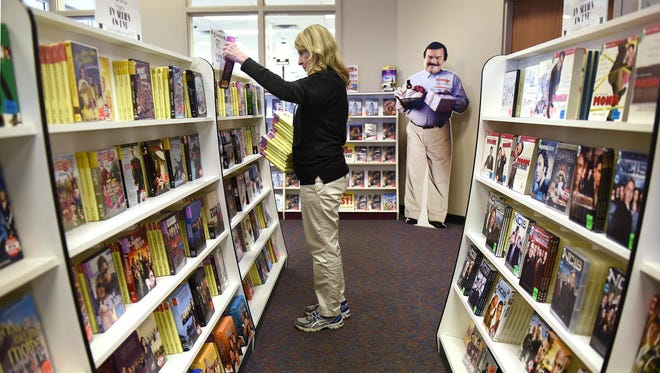 Nita Schneider returns DVDs to the shelves in the television series section on July 15 at Cash Wise Video in Waite Park.