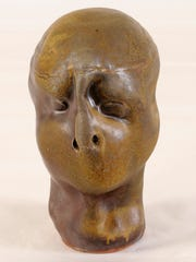 """A ceramic head from the Mary Bowron collection donated by the Kohler Foundation to the UW-Sheboygan campus. The heads designed with """"no mouth for fear of speaking what they say and hear"""" will serve as a springboard for discussions in diversity and social justice."""