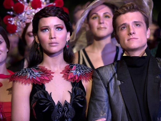 Katniss Everdeen is heading back into the arena, poised to battle her fellow victors in 'The Hunger Games: Catching Fire.' Costume designer Trish Summerville made sure our heroine had the threads to go the distance, estimating that Jennifer Lawrence (pictured with co-star Josh Hutcherson) alone had 40 to 50 costume changes. USA TODAY's Andrea Mandell found the Girl on Fire's looks we love for less.