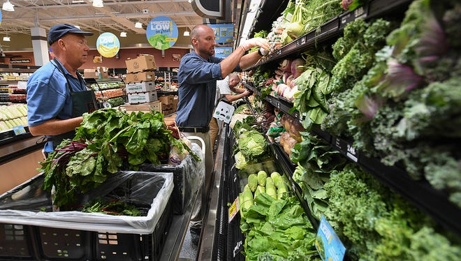 Brice Mollohan, right, and Gerald Waldrop stock the produce at the new Harris Teeter grocery store on Augusta Street in Greenville Tuesday, July 10, 2018. The store is scheduled to open Wednesday.