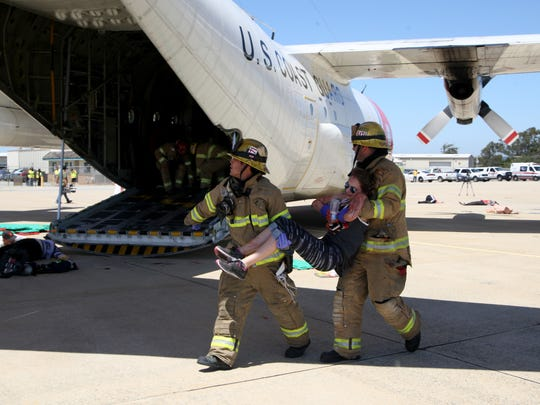 """Firefighters carry a """"patient"""" to safety during an emergency response drill on Tuesday."""