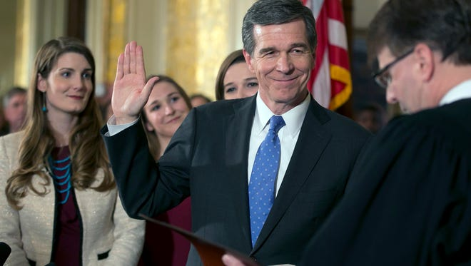 Roy Cooper is ceremonially sworn in as governor of North Carolina by Chief Justice Mark Martin during a ceremony on Friday at the Executive Mansion in Raleigh. Cooper's daughters from left, Hilary, Natalie and Claire look on. The swearing in ceremony, originally scheduled for Saturday, was canceled and moved to Friday due to a winter storm that is expected to move through Raleigh overnight. (Robert Willett/The News & Observer via AP)