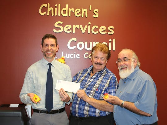 Everything is Just Ducky as Sean Boyle, Children's Services Council executive director, presents Fort Pierce Jazz and Blues Society President Don Bestor a check to help fund Just Ducky, an upcoming event for families in St. Lucie Couty. Children's Services Council's Jim Dwyer looks on.
