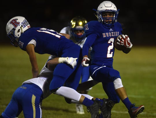 Reno's Anthony Hill (2) runs while taking on Reed during