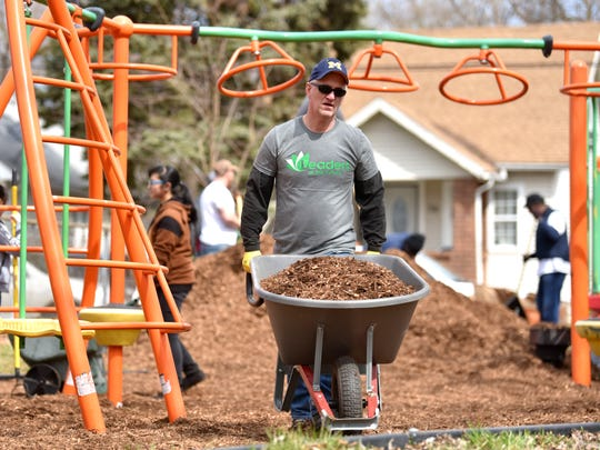 Tim Fisher, of Macomb Twp., wheels mulch to dump on the play ground.