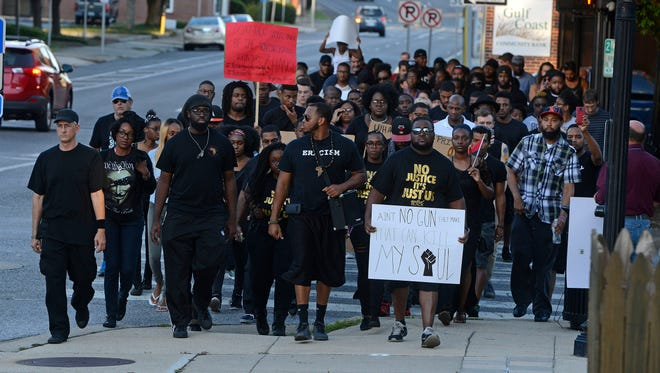 Marchers make their way to the MC Blanchard Judicial Building Saturday during the Black Lives Matter Walk which started at the Martin Luther King Memorial and ended at the MC Blanchard Judicial Building with a momnet of silence.