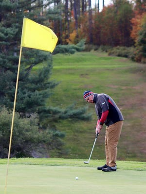 Bill Wilson, shown putting on the 18th green, and teammate Chris Murphy edged out Alek Dernalowicz and Ryan Pasakinskas by a half point to win the A flight of the ninth annual Columbus Day Weekend Four Ball tournament, Monday, at Gardner Municipal Golf Course.