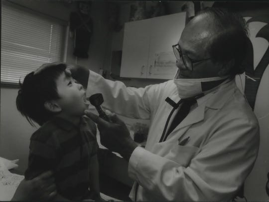 In this 1994 photo Marciano Visaya checks Titus Thao, 4, at the Milwaukee Immediate Care Center, 1971 W. Capitol Drive. City officials are evicting the clinic for non-payment of property taxes.