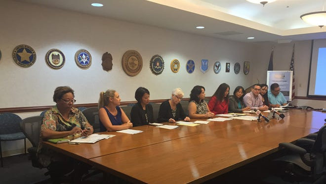 U.S. Attorney Alicia A.G. Limtiaco, in red, sits with nine of the more than 60 community stakeholders, at a press conference held at the U.S. Attorney's Office on Monday to discuss the upcoming Workforce Development Training.