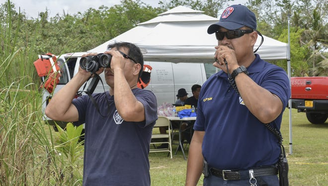 Capt. Alex Castro, incident commander, right, and Mike sanchez of the Guam Fire Department search for a missing fisherman at the Agat cemetery command post on June 10.