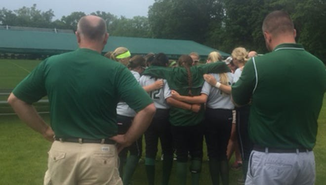The Wayland Union softball team huddles after beating St. Clair on Thursday, June 11, 2015, in East Lansing.