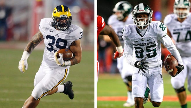 Michigan fullback Sione Houma, left, and Michigan State receiver Macgarrett Kings Jr.