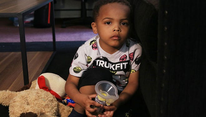 Zaviyon Scott, 4, holds one of his inhalers, which he uses 6 times per day.