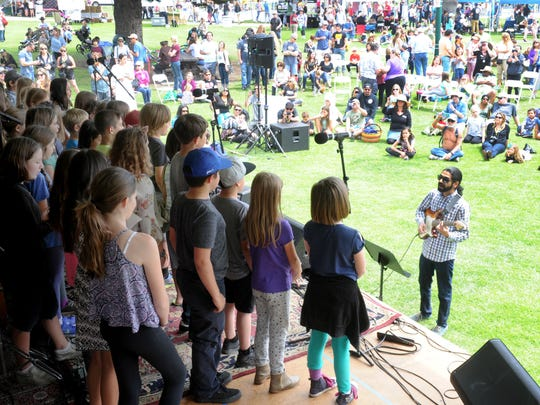 "Students from Ventura Charter School sing ""Fields of Gold"" as music teacher Sandesh Nagaraj helps them out by playing guitar during a past Earth Day celebration at Plaza Park in Ventura."